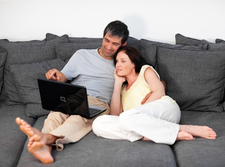 Lovely couple using a laptop on a sofa Stock Photo - 10248813