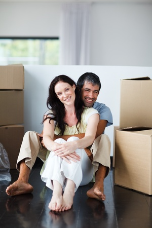 Smiling couple sitting in their new house photo