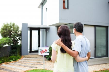 buying a home: Newlyweds with their new house Stock Photo