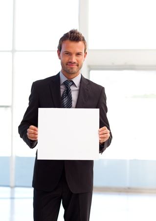 Friendly businessman holding a white card photo