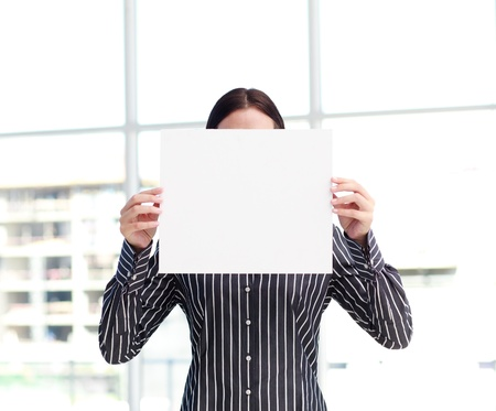 Smiling woman showing a big business card in front of her face photo