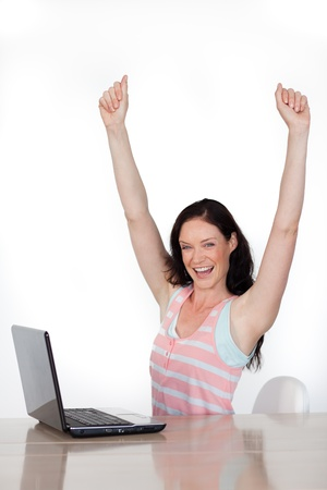 Happy woman using a laptop against a white background photo