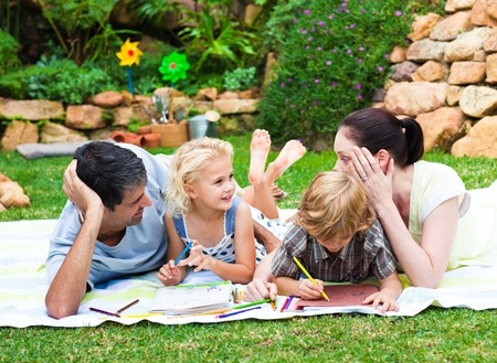 Happy family drawing together in a park photo