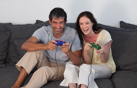 Laughing couple playing video games photo