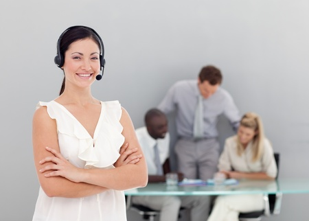 Businesswoman talking on a headset with folded arms photo