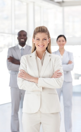 Portrait of a serious businesswoman standing with her collegues photo