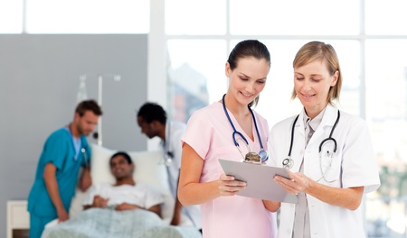 insurance consultant: Group of doctors attending to a patient Stock Photo