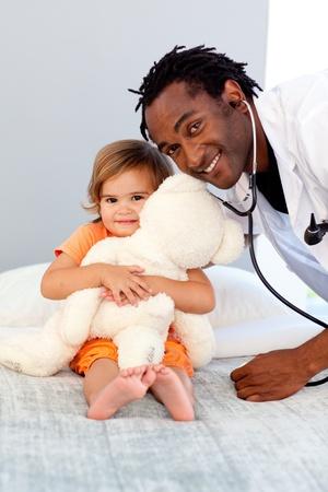 enfermera con paciente: Doctor sonriente examinar a una ni�a en el hospital Foto de archivo