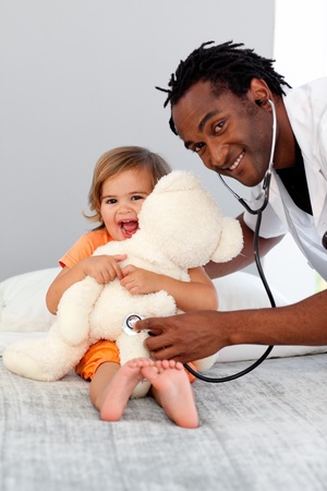 Happy doctor examining a little girl at hospital photo