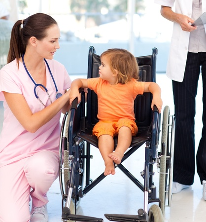 consulting room: Young nurse talking to a baby in a wheelchair