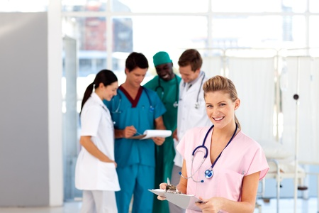 Beautiful nurse with her team in the background photo