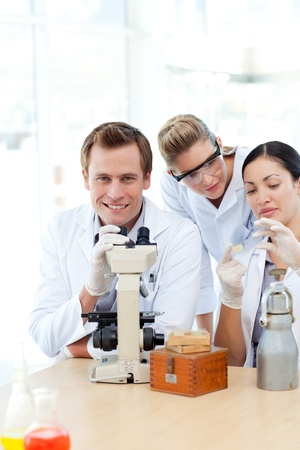 Scientists looking at a slide under a microscope Stock Photo - 10249424