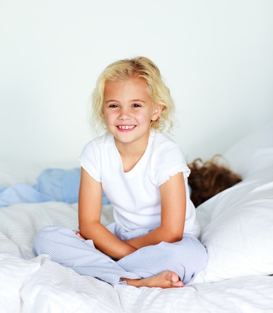 Little girl sitting on bed smiling at the camera photo