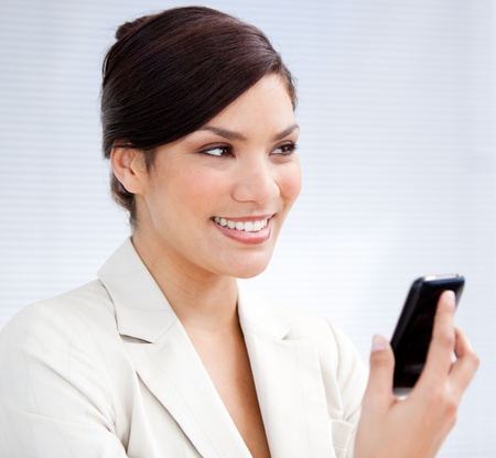 Radiant businesswoman using a mobile phone Stock Photo - 10246104
