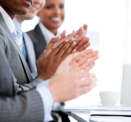 Close up of a  mixed business team applauding a presentation  photo