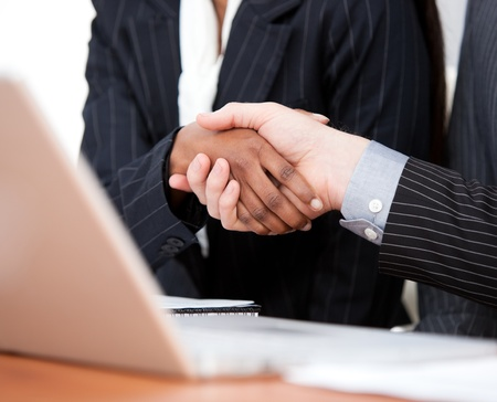 Close-up of a handshake between two businessmen with laptop photo