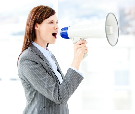 assertive: Portrait of an beautiful businesswoman using a megaphone  Stock Photo