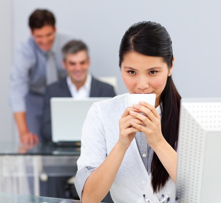 Brunette woman drinking coffee in the office photo