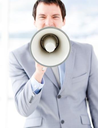 businessman using a megaphone: Portrait of an nervous businessman using a megaphone Stock Photo