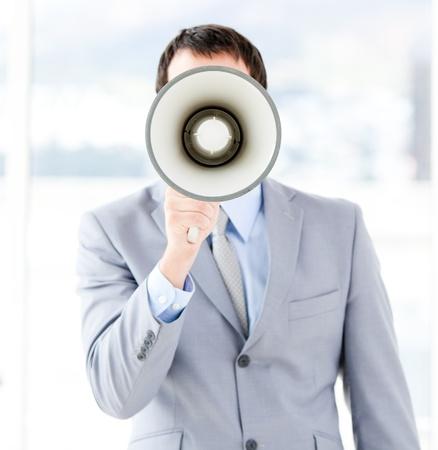 businessman using a megaphone: Portrait of an young businessman using a megaphone