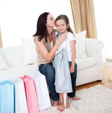Mother kissing her little girl after shopping photo