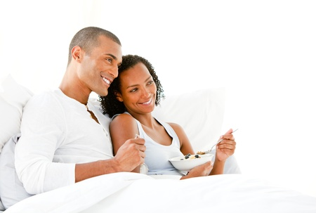 Loving couple having breakfast lying on their bed  photo