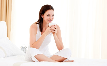 drinking tea: Beautiful woman drinking a coffee sitting on her bed