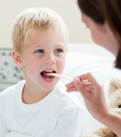 A doctor examining a childs throat  photo