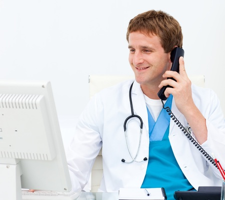 Close-up of a doctor on phone at a computer photo