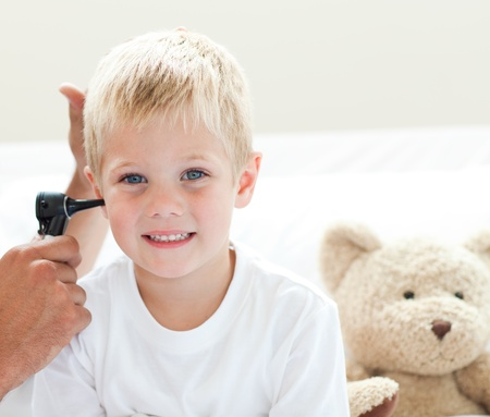 A doctor examining a smiling little boy's ears Stock Photo - 10233924