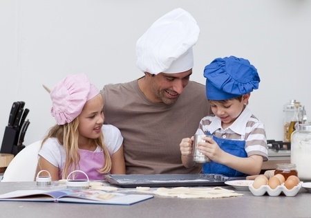 Father and children baking in the kitchen photo