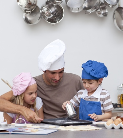 Father baking cookies with his children photo
