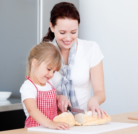 Portrait of a smiling mother and his daughter preparing a meal photo