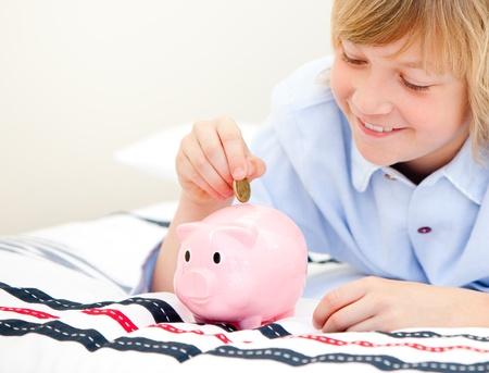 piggybank: Cute boy putting a coin in a piggybank