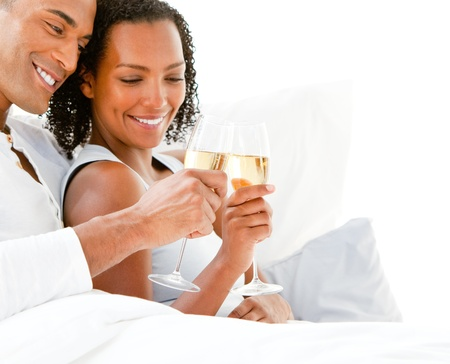 luxury bed: Affectionate couple toasting with Champagne lying on their bed