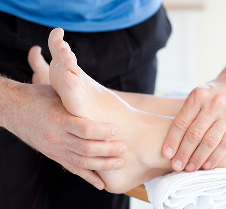 masaje deportivo: Primer plano de una mujer que disfruta de un masaje de pies  Foto de archivo