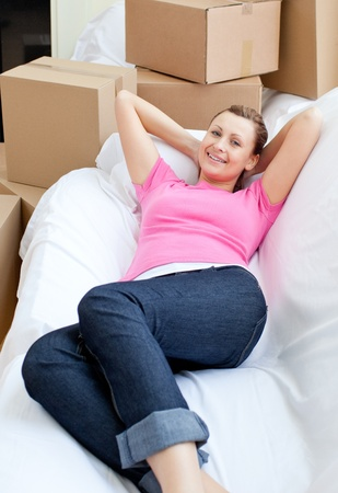 Beautiful woman relaxing on a sofa with boxes photo
