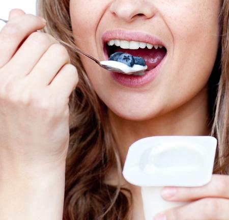 Beautiful woman eating a yoghurt photo