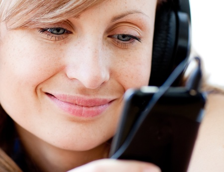 Portrait of a delighted woman listening the music with headphones  photo