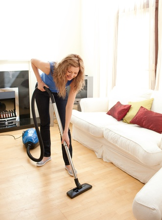 Happy woman cleaning her living room photo