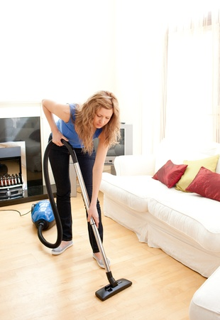 bright housekeeping: Disintersest woman cleaning her living room Stock Photo