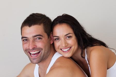 pareja en la cama: Joven pareja sonriendo a la c�mara