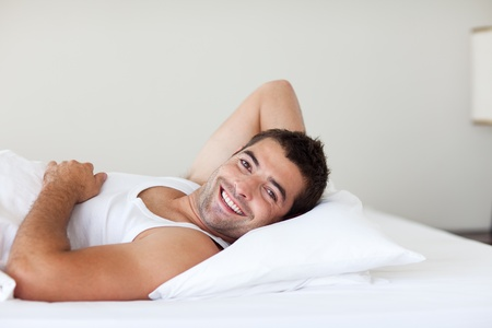 Attractive man in a bed smiling at the camera photo