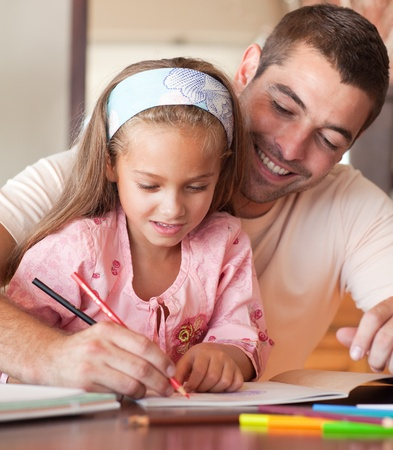 Father and cute daughter drawing together photo