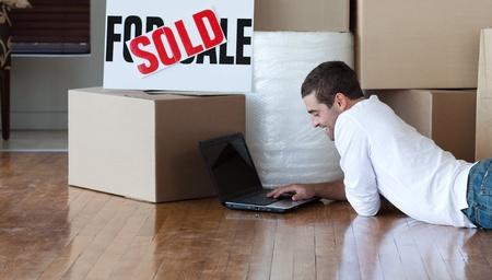 vendiendo: Hombre hermoso trabajando en su computadora port�til en el piso Foto de archivo