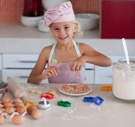 Merry little girl baking biscuit photo