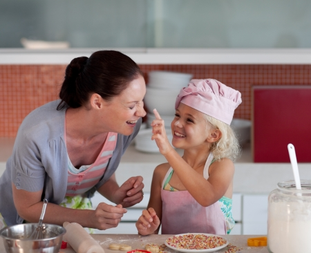 baking cookies: Potrait of mother and daugther having fun together