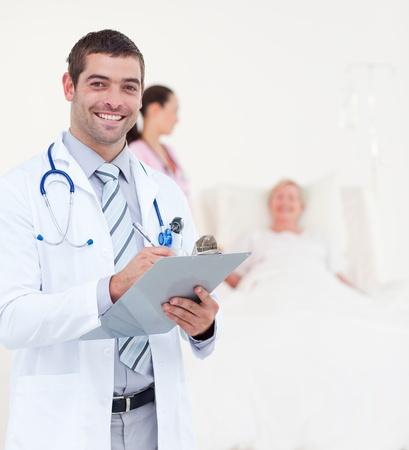Succesvolle mannelijke arts schriftelijk op de clip boord