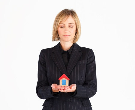 Smiling mature businesswoman holding a house photo