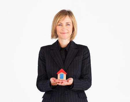 Pretty mature businesswoman holding a house photo